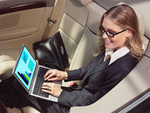Donna di affari in sua automobile con il computer portatile Fotografia Stock