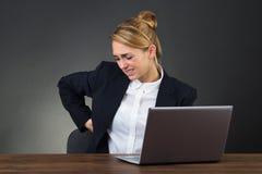 Donna di affari Suffering From Backpain mentre per mezzo del computer portatile fotografie stock libere da diritti