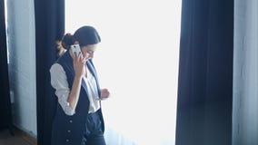 Donna di affari sul cellulare che parla, mentre per mezzo dell'altro smartphone Fotografia Stock