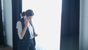 Donna di affari sul cellulare che parla, mentre per mezzo dell'altro smartphone stock footage