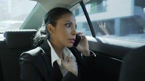 Donna di affari sul sedile posteriore dell'automobile, discutendo a fondo telefono, pettegolante con l'amico stock footage