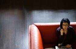 Donna di affari sul sofà d'angolo Immagini Stock