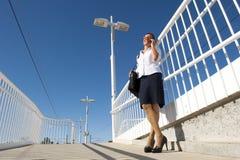 Donna di affari sul telefono alla stazione ferroviaria Immagini Stock