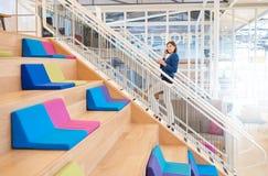 Donna di affari sul telefono che cammina sulle scale con caffè asportabile Fotografia Stock Libera da Diritti