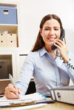 Donna di affari sul telefono che cattura le note Immagine Stock