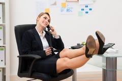 Donna di affari sul telefono con i piedi sullo scrittorio fotografie stock