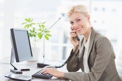 Donna di affari sul telefono e sul per mezzo del suo computer Fotografia Stock Libera da Diritti