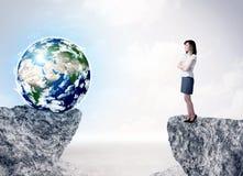 Donna di affari sulla montagna della roccia con un globo Fotografie Stock