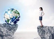 Donna di affari sulla montagna della roccia con un globo Immagini Stock Libere da Diritti