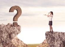 Donna di affari sulla montagna della roccia con un punto interrogativo Fotografia Stock