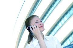 Donna di affari sulla tinta dell'azzurro del telefono delle cellule Immagini Stock