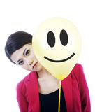 Donna di affari triste attraente dietro un fronte di smiley Fotografia Stock