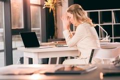 Donna di affari turbata in vestito che si siede alla tavola in ufficio Immagini Stock