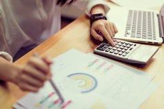 Donna di affari in ufficio e computer e calcolatore di uso per eseguire conto finanziario immagini stock libere da diritti
