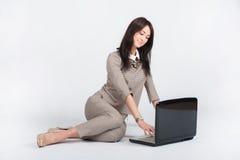 Donna di affari in un vestito grigio che lavora con un computer portatile immagini stock
