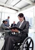 Donna di affari in una sedia a rotelle che legge un rapporto Immagine Stock