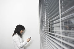 Donna di affari Using Cellphone In Front Of Window Blinds immagini stock libere da diritti