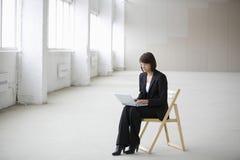 Donna di affari Using Laptop While che si siede sulla sedia in magazzino Fotografia Stock Libera da Diritti