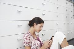 Donna di affari Using Mobile Phone mentre sedendosi contro i cassetti Immagine Stock Libera da Diritti