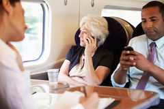 Donna di affari Using Mobile Phone sul treno pendolare occupato Fotografia Stock Libera da Diritti