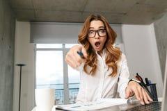 Donna di affari vestita in camicia convenzionale dei vestiti all'interno facendo uso del computer portatile che indica voi fotografie stock libere da diritti