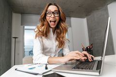 Donna di affari vestita in camicia convenzionale dei vestiti all'interno facendo uso del computer portatile fotografia stock libera da diritti