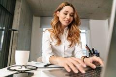 Donna di affari vestita in camicia convenzionale dei vestiti all'interno facendo uso del computer portatile immagine stock