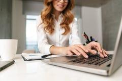Donna di affari vestita in camicia convenzionale dei vestiti all'interno facendo uso del computer portatile immagine stock libera da diritti