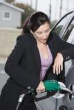 Donna di affari in vestito che rifornisce di carburante la sua automobile Immagini Stock