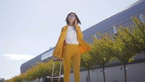 Donna di affari in vestito ed occhiali da sole che parlano sullo smartphone mentre camminando con il bagaglio a mano vicino alla  video d archivio