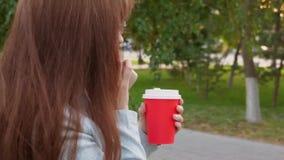 Donna di affari in vetri che parla sul caffè di risata e bevente dello smartphone mentre camminando nel parco Primo piano video d archivio