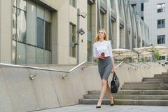 Donna di affari Walking On Street e tenere caffè caldo Fotografia Stock