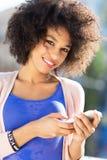 Donna di afro che per mezzo del telefono cellulare Fotografia Stock