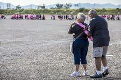 Donna di aiuti dell'uomo messa sul superstite Sash alla passeggiata del cancro al seno fotografia stock