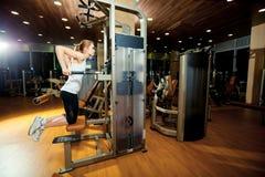 Donna di allenamento di esercizio delle immersioni del tricipite della palestra dell'interno Fotografia Stock