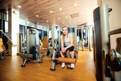 Donna di allenamento di esercizio di estensione della gamba della palestra dell'interno Fotografia Stock