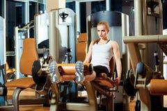 Donna di allenamento di esercizio di estensione della gamba della palestra dell'interno Immagini Stock