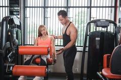 Donna di allenamento di esercizio di estensione della gamba della palestra con l'istruttore Immagine Stock