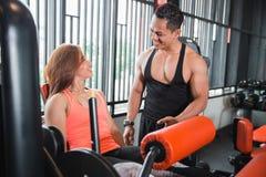 Donna di allenamento di esercizio di estensione della gamba della palestra con l'istruttore bello Fotografia Stock