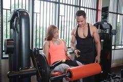 Donna di allenamento di esercizio di estensione della gamba della palestra con l'istruttore personale Fotografie Stock Libere da Diritti
