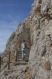 Donna di alpinismo, scalante una strada fatta un passo nelle alpi Immagini Stock
