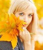 Donna di autunno con le foglie di acero gialle di caduta Fotografia Stock