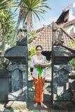 Donna di balinese che indossa i vestiti tradizionali che portano i sari del canang immagini stock libere da diritti
