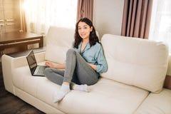 Donna di Bbeautiful che per mezzo del computer portatile a casa sul sof? fotografia stock