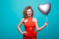 Donna di bellezza in attrezzatura rossa operata che posa sulla macchina fotografica con impulso di forma del cuore, sopra la pare fotografia stock libera da diritti