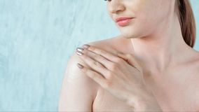 Donna di bellezza che applica crema sulla sua spalla nella stanza leggera stock footage