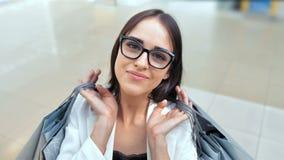 Donna di bellezza con i sacchetti della spesa che posano nel centro commerciale leggero moderno video d archivio