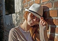 Donna di bellezza con il cappello bianco in un vicolo romantico Immagine Stock