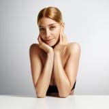 Donna di bellezza con pelle ideale sui precedenti beige che toccano il suo fronte Immagine Stock Libera da Diritti
