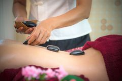 Donna di bellezza dell'Asia che si riposa sul letto di massaggio con il alon caldo delle pietre di balinese tradizionale Fotografia Stock